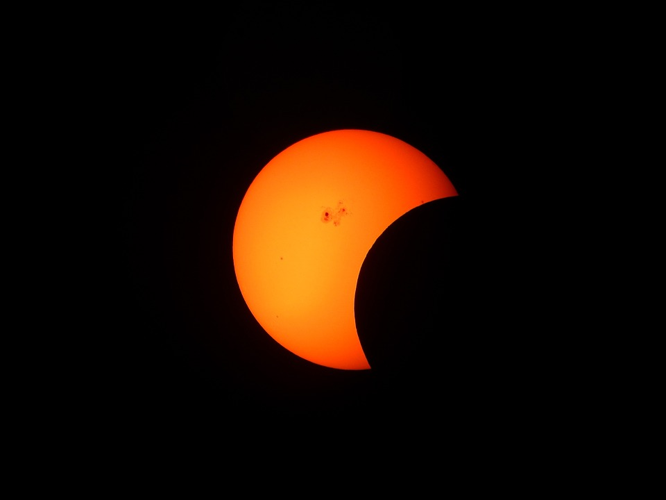 sun passing over a red moon in a solar eclipse
